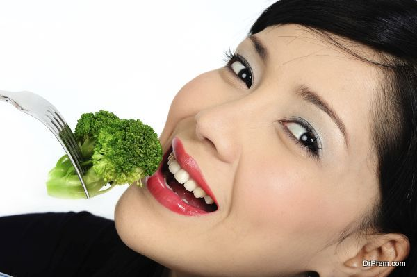 Beautiful young asian girl eating broccoli