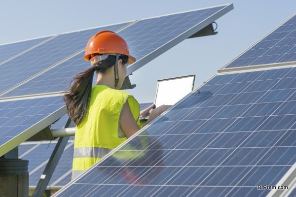 A woman in orange helmet is standing beside the solar energy panel and using the notebook