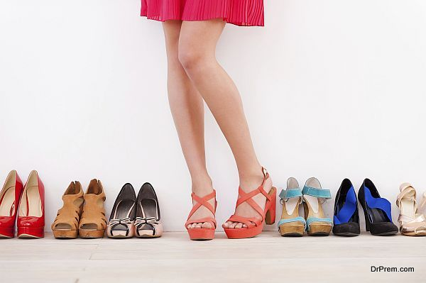 She made her choice. Cropped image of young woman in high heeled shoes standing against the wall while more shoes laying in a row near her