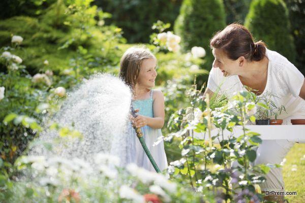 Girl and granny watering flowers in garden