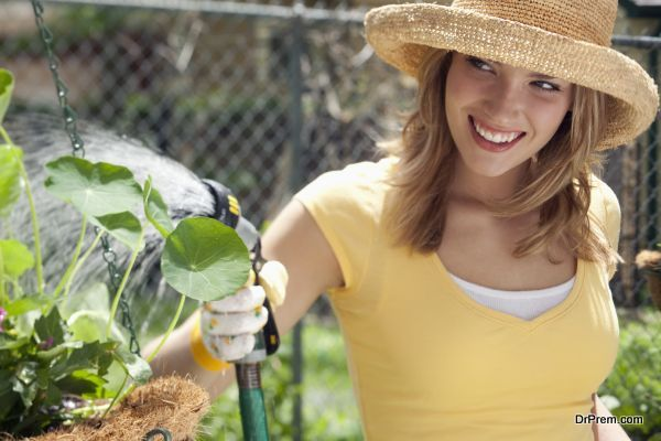 Smiling young woman watering flowers in the garden