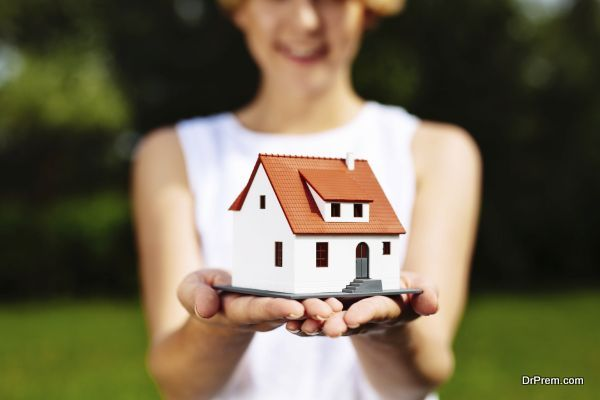 Photo of a young woman holding a miniature house
