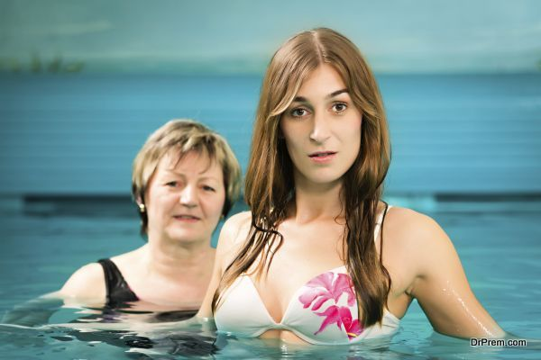 Wellness - mature and young woman swimming in swimming pool or doing water gymnastics, also a concept for wells of youth