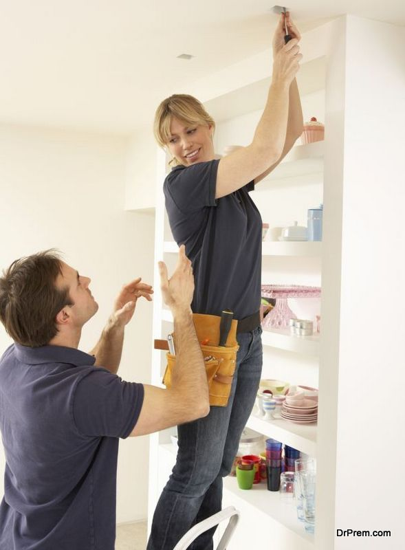 Electrician Teaching Apprentice To Install Light Fitting In Home