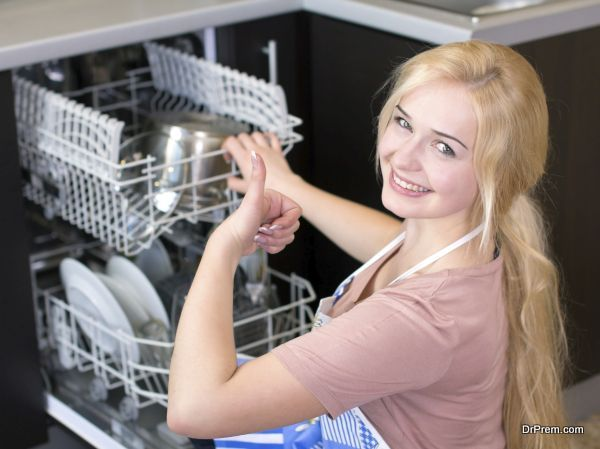 Kitchen Woman. Girl in the kitchen using dishwasher. view of young woman in kitchen doing housework.