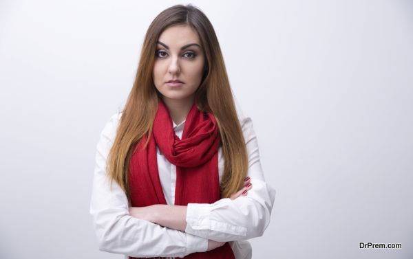 Portrait of a young woman with arms folded looking at camera