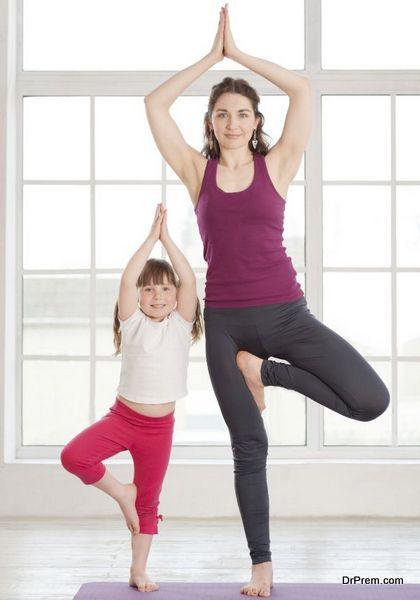 Young mother and daughter doing yoga exercise in fitness studio with big windows on background