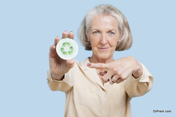 Portrait of senior woman holding badge with recycling symbol against blue background