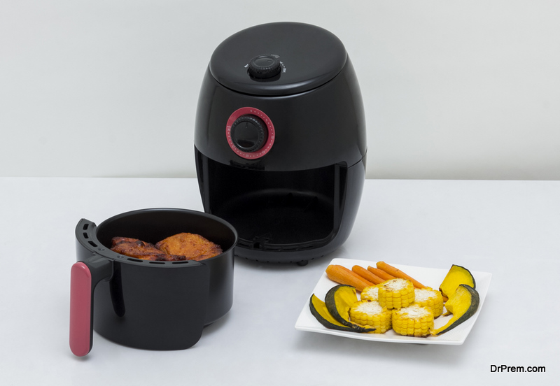 Air fryer machine with chicken and vegetables