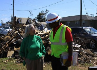 Joseph Rodrigues from Mobile District talks with a homeowner about the damage to her home.