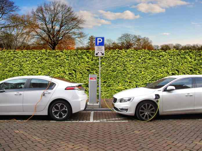 Two white electric cars charging at a charging station