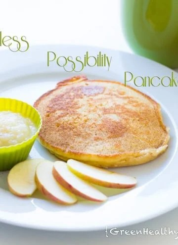 A pancake on a white plate with sliced apples and apple sauce in a small green bowl.