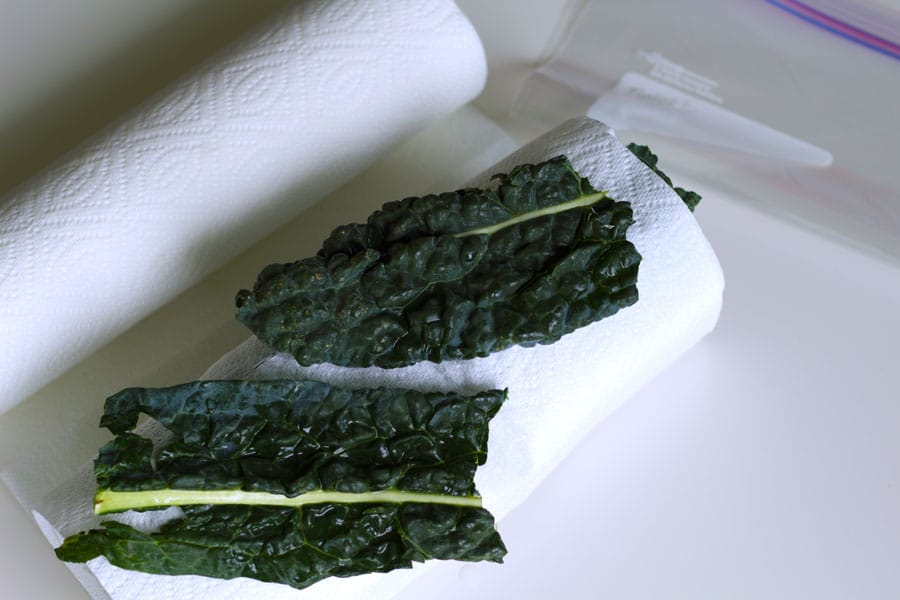 Two green leaves being rolled with a paper towel roll next to a resealable plastic bag.