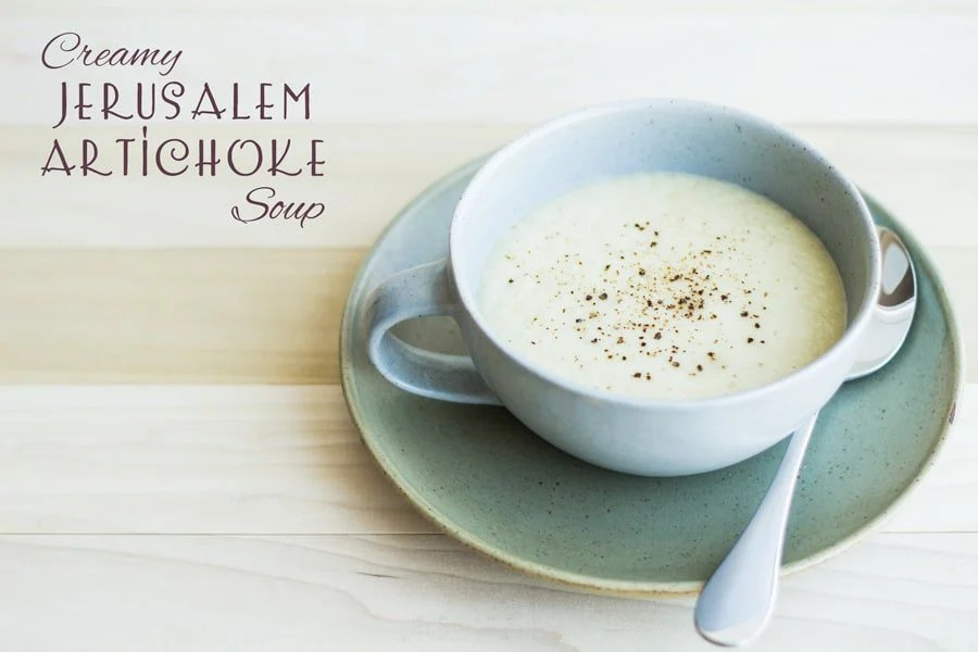 Creamy Jerusalem Artichoke Soup in a green bowl on a plate with a spoon with text overlay.