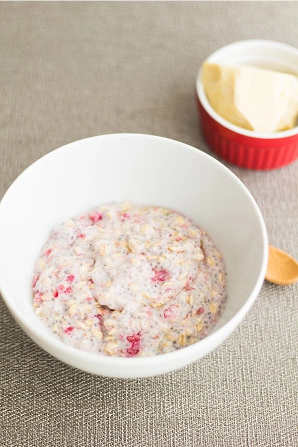 Ingredients for Raspberry White Chocolate Overnight Oats mixed in a white bowl.