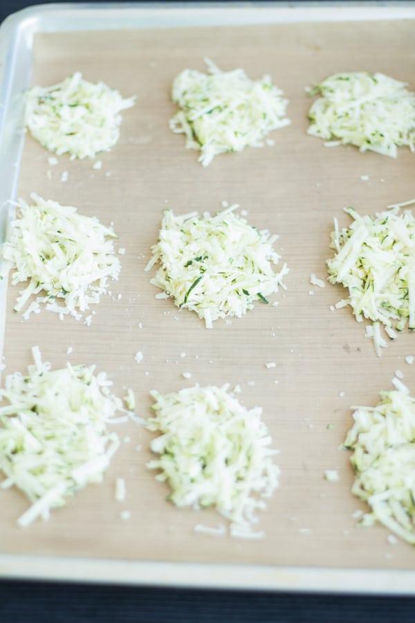 Parmesan Gruyere Zucchini Crisps laid out on baking sheet.