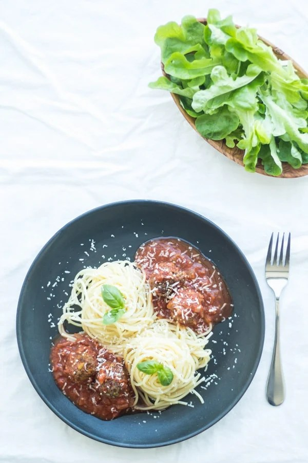 Spaghetti with Pistachio Meatballs on a black plate, a fork and a bowl with green leaves.