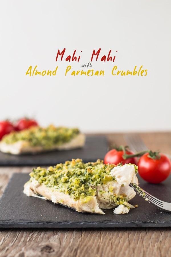 Mahi Mahi con mandorle e parmigiano sbriciolato servito su piatti quadrati neri su un tavolo di legno e forchetta che tiene un pezzo di cibo.