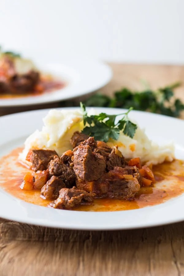 Tender Lamb Stew with Homemade Potato Mash on a white plate on a wooden table.