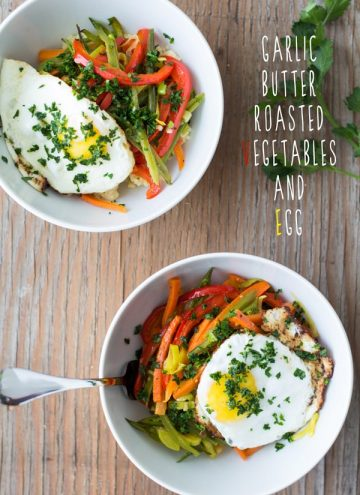 Top view of Garlic Butter Roasted Vegetables and Egg in white bowls on a wooden table with text overlay.