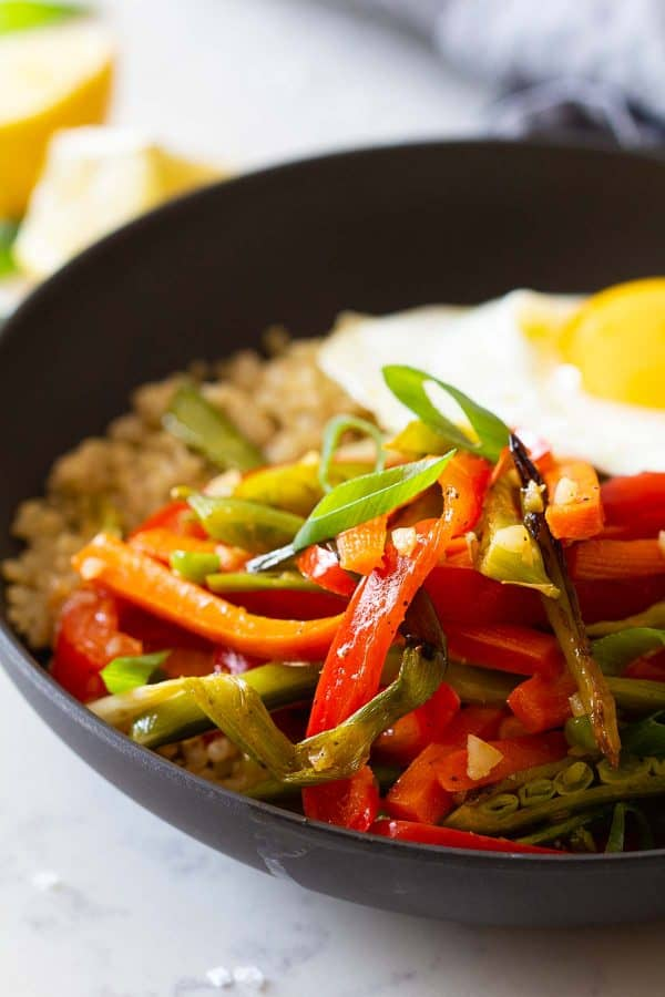Closeup of sliced roasted vegetables in a bowl on quinoa and topped with a fried egg.