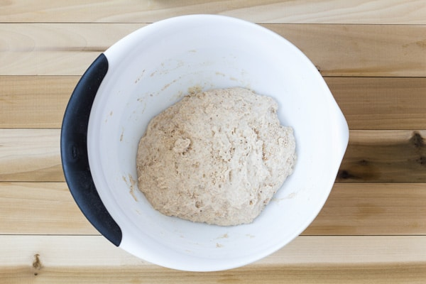 Mixed ingredients for No-Kead Sesame Seed Bread in a white bowl on a wooden table.