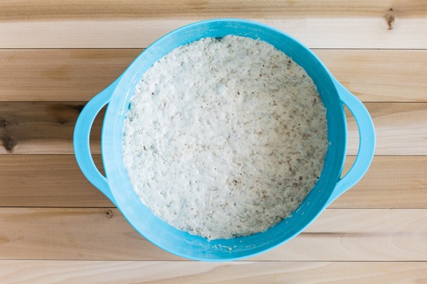 No-Knead Sesame Seed Bread dough after first rise in a blue bowl on a wooden table.