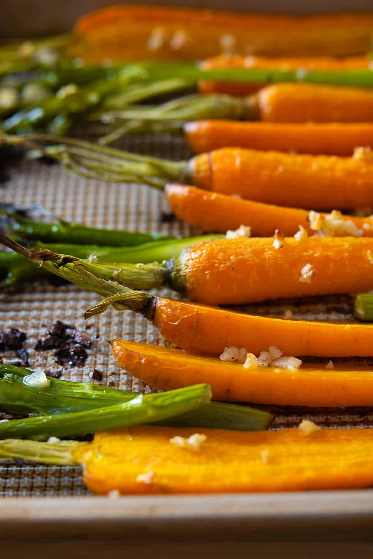Close up of texture of roasted carrots and broccolini on a baking sheet.