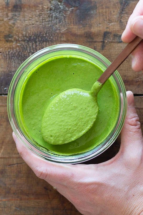 green sauce in jar and spoon lifting up green sauce