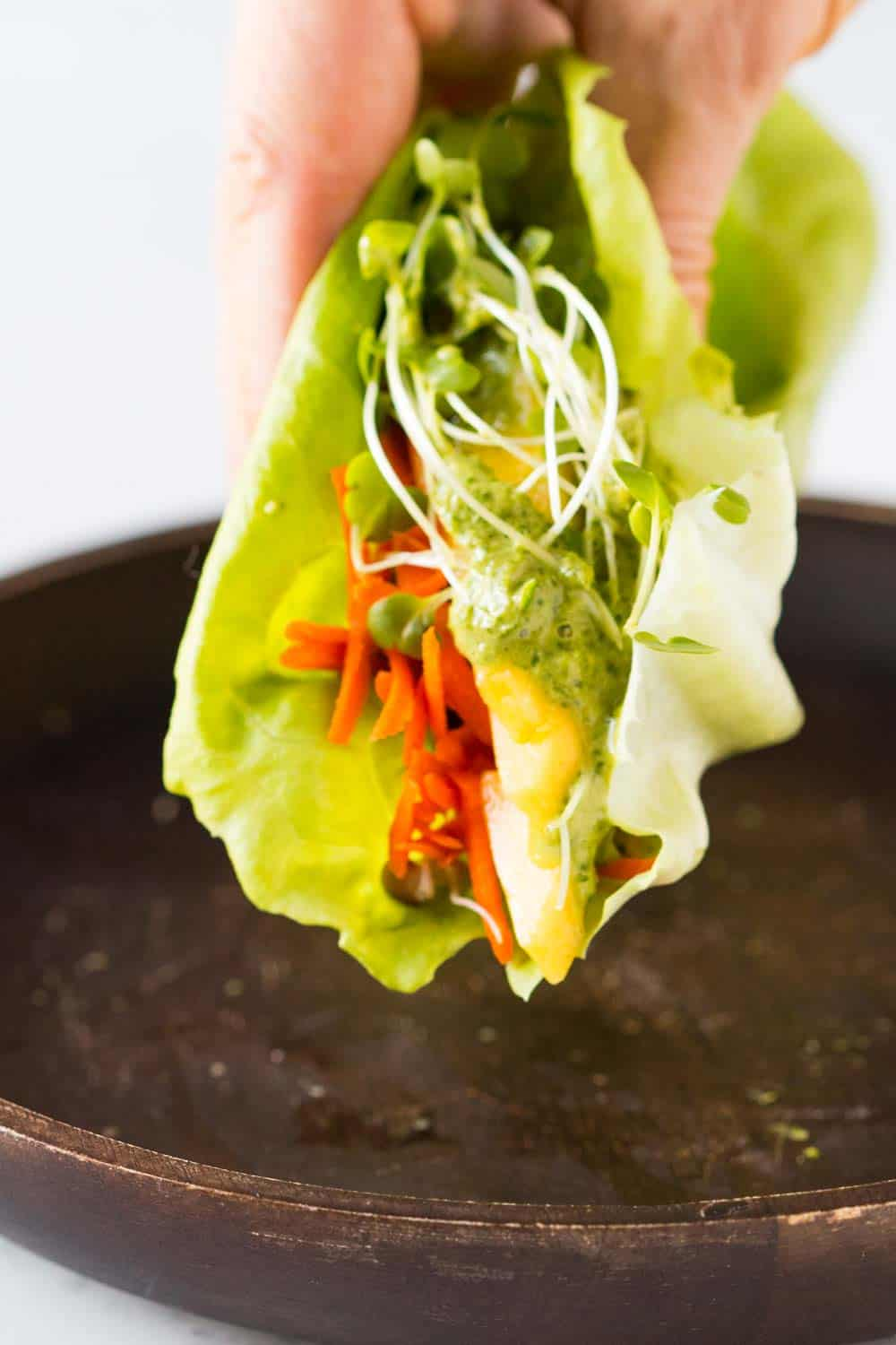 Close up of vegan lettuce wrap with tahini herb sauce