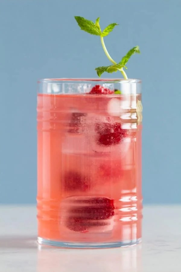 Pink Lemonade, ice cubes, raspberries, and mint in a glass