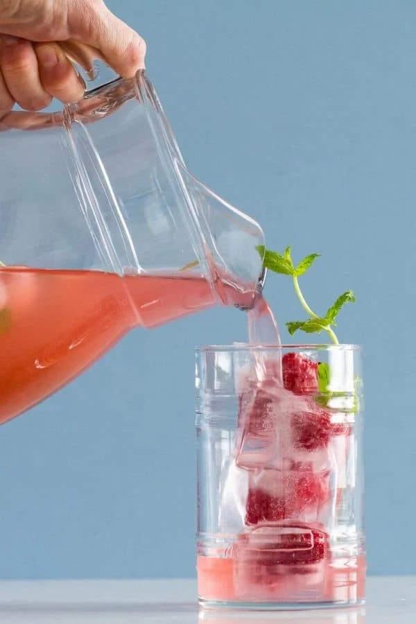 Pink Lemonade poured from a pitcher into a glass filled with ice, raspberries and mint