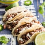 Close up of Pinto Bean Tacos with Salsa Verde on a rustic wood board with text overlay.
