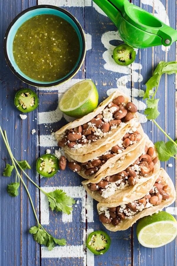 Top view of Pinto Bean Tacos with Salsa Verde and limes on a rustic wood board.