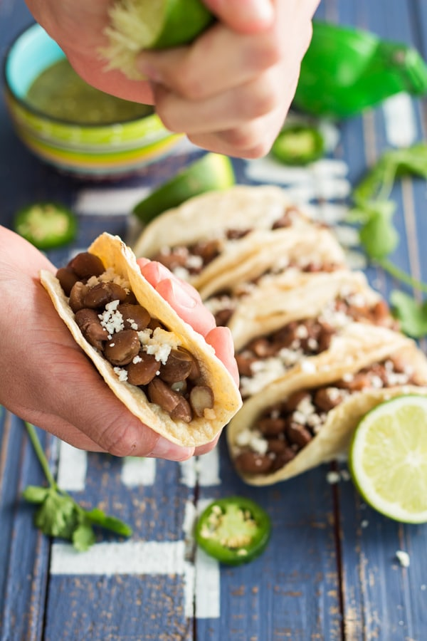 Hand holding a Pinto Bean Taco squeezing lime juice on it.