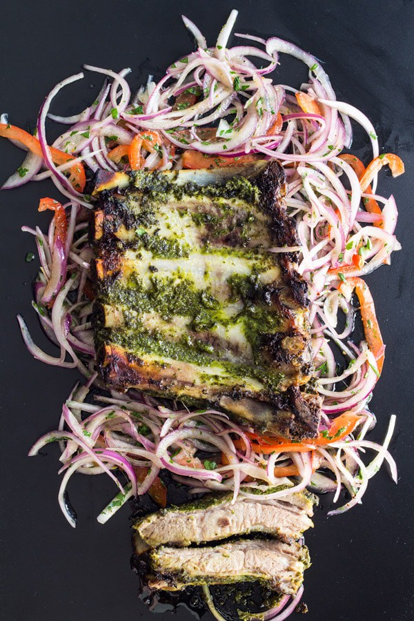 Top view of cooked Spare Ribs on Salsa Criolla on a bed of shredded veggies on a black background.