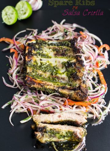 Top view of cooked Spare Ribs on Salsa Criolla on a bed of shredded veggies on a black background with text overlay.