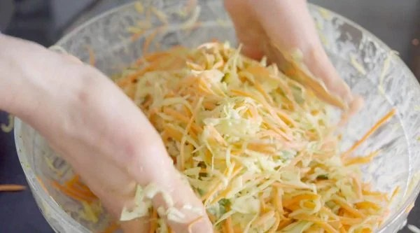 mixing slaw with hands