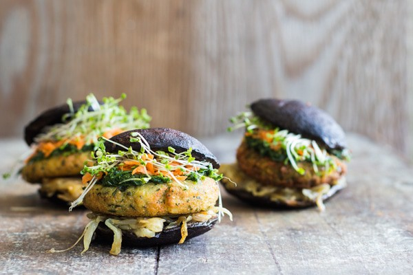 Three Portobello Burgers on a wooden board.