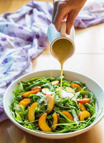 Hand pouring dressing over Arugula and Nectarine salad.