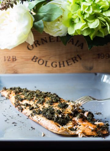 Dill Butter Baked Salmon on a square plate and some flowers on top.