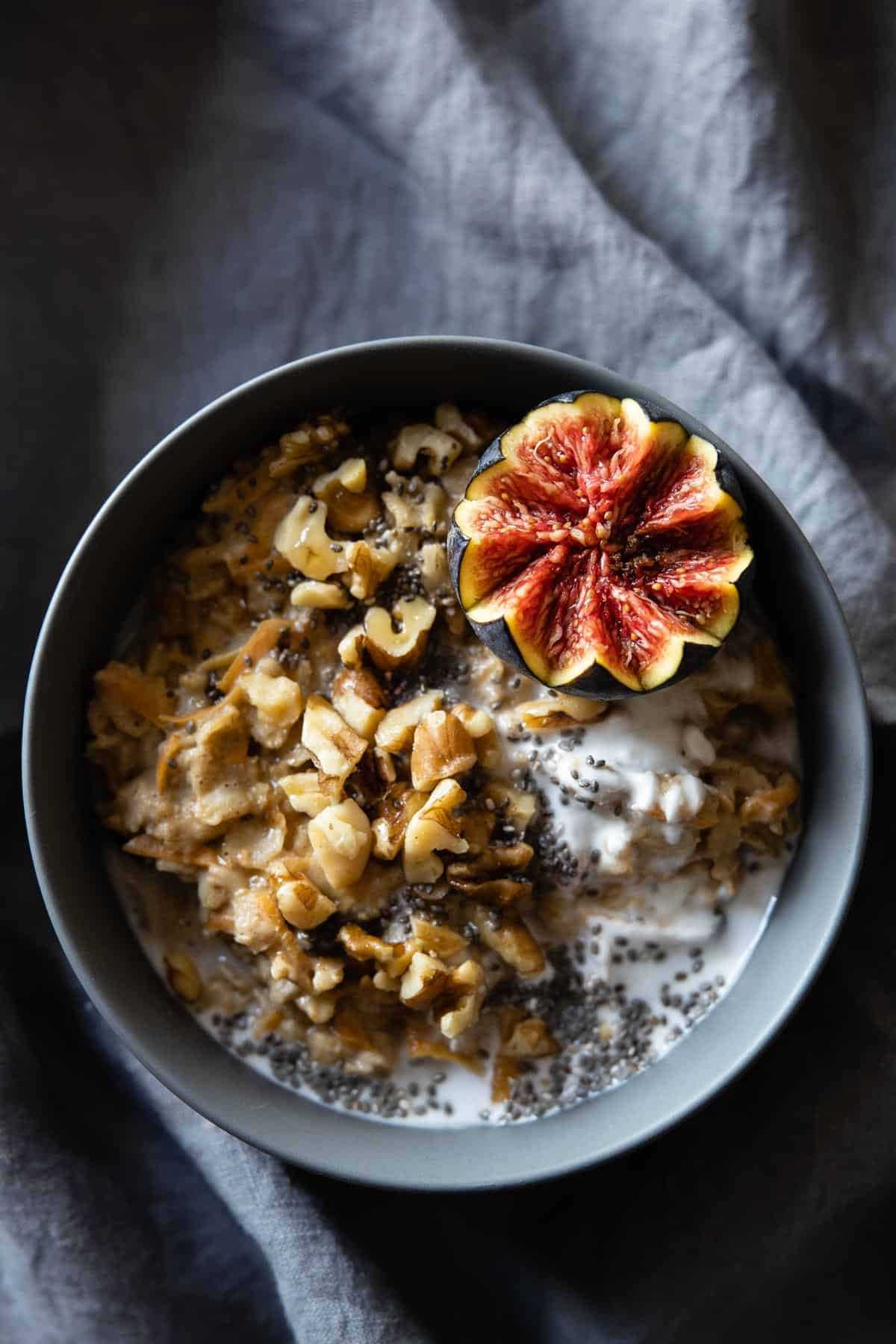 Carrot cake oatmeal in a grey bowl topped with chopped walnuts and half a fig.