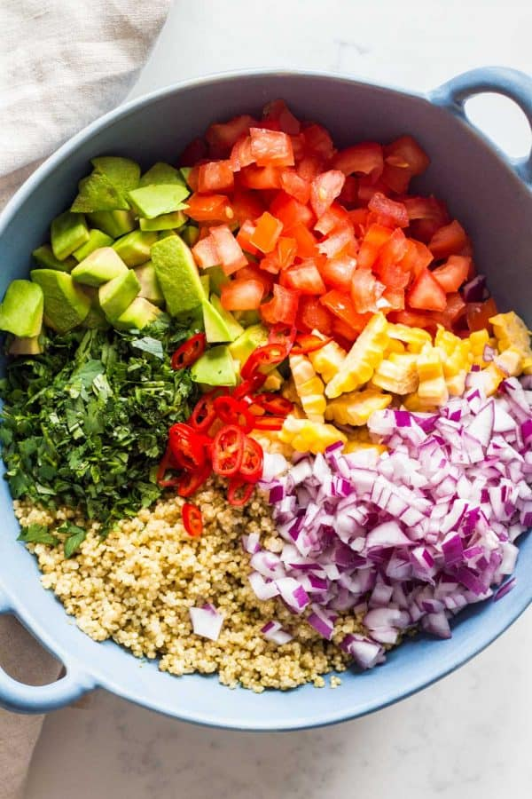 mexican quinoa salad with avocado in large blue salad bowl