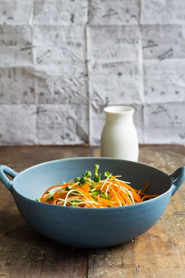 Sunflower Carrot Salad in a blue bowl with a white dressing jar in the background on a wooden board.