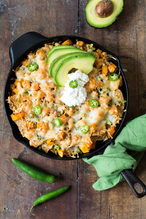 Top view of Butternut Squash Nachos in a black skillet garnished with sliced avocado on a wooden board.