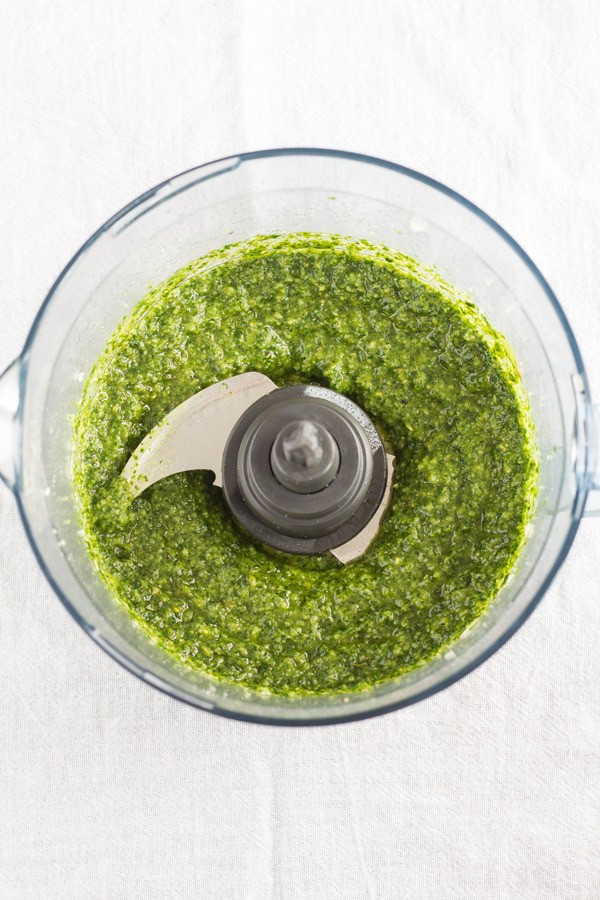 Top view of Ingredients for herb pesto sauce blended in an open food processor.
