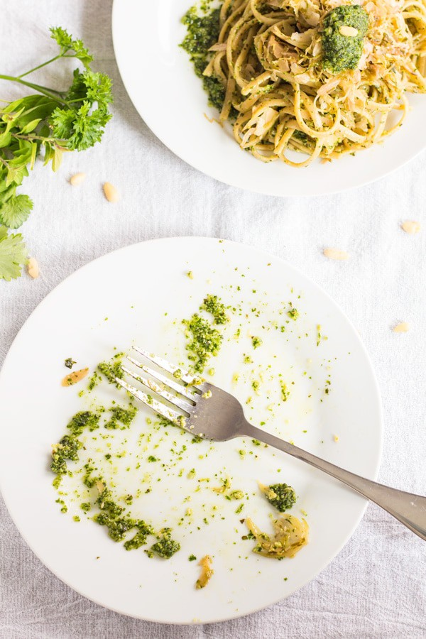 A plate of Shaved Brussels Sprouts Pasta with Herb Pesto and an empty plate of eaten pasta with a fork.