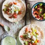 Shrimp Tacos with Cilantro Lime Salsa, a cup of salsa and a cup of chopped tomatoes.