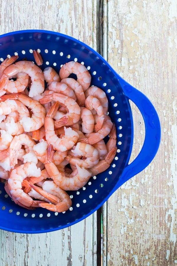 Shrimps in a blue strainer basket.