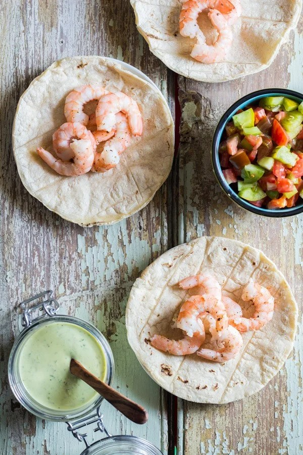 Shrimp Tacos with a small cup of Cilantro Lime Salsa and a cup of chopped tomatoes on a rustic wooden board.